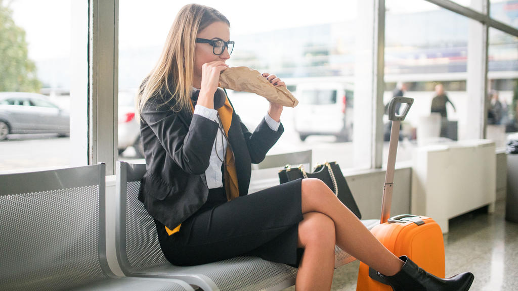 Frau sitzt in der Wartehalle des Flughafens und isst.