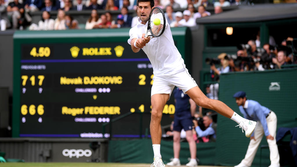 LONDON, ENGLAND - JULY 14: Novak Djokovic of Serbia plays a backhand in his Men's Singles final against Roger Federer of Switzerland during Day thirteen of The Championships - Wimbledon 2019 at All England Lawn Tennis and Croquet Club on July 14, 201