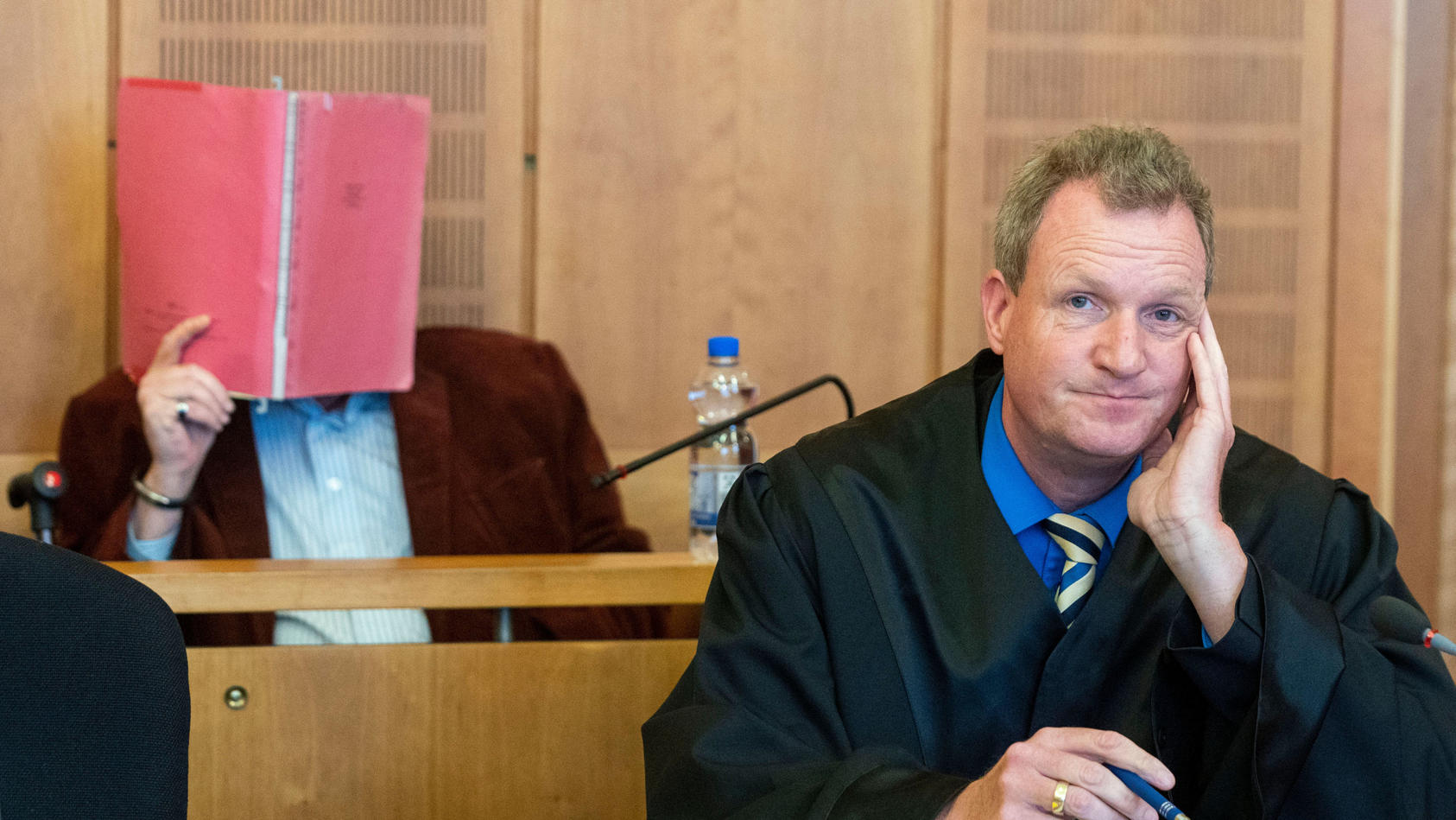 Der Angeklagte (hinten) sitzt mit seinem vor Prozessbeginn im Gerichtssaal des Landgerichts Krefeld.