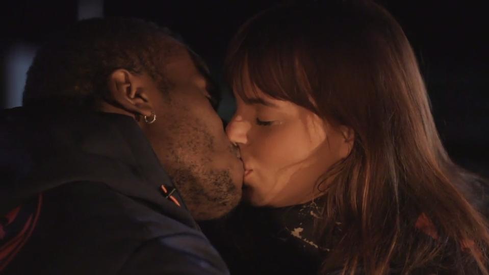 Mo und Michelle küssen sich beim Lagerfeuer am Meer.