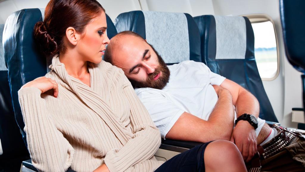 Mann schläft auf Schulter von Sitznachbarin im Flieger ein.