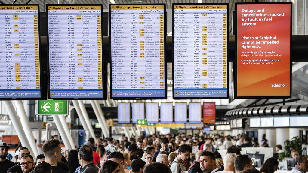 """24.07.2019, Niederlande, Amsterdam: Zahlreiche Fluggäste warten am Flughafen Schiphol unter Anzeigetafeln mit einem Hinweis: """"Delays and cancellations caused by fault in fuel system. Planes at Schiphol cannot be refuelled right now."""" (Verspätungen un"""
