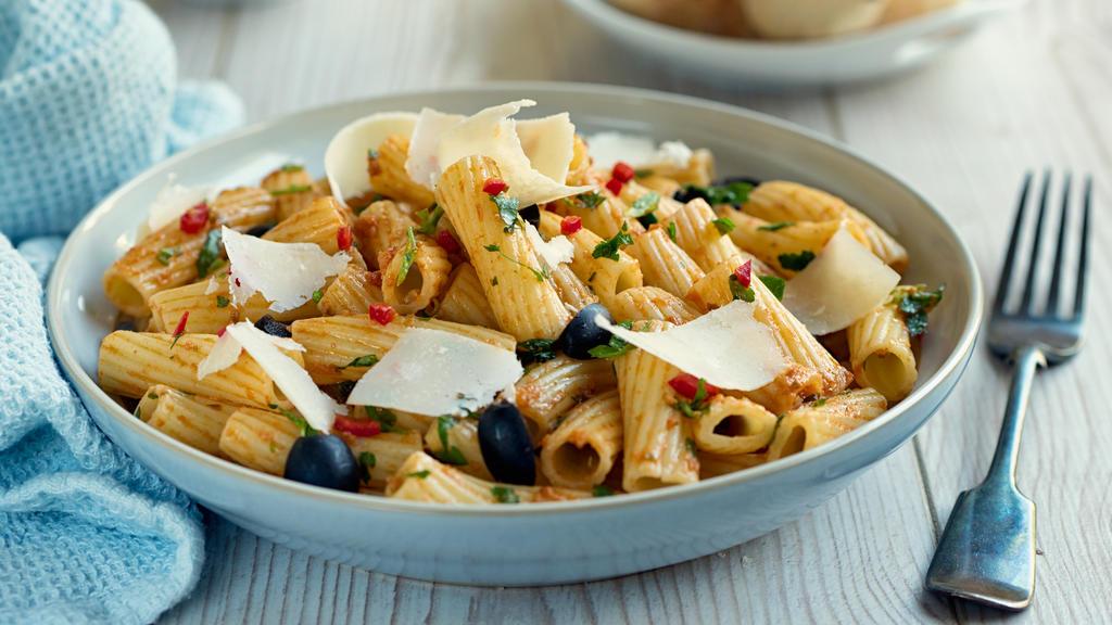 Italienischer Nudelsalat mit rotem Pesto, Parmesankäse und Oliven.