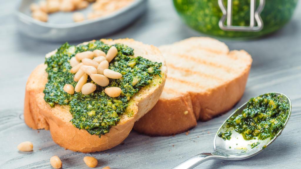 Baguette mit grünem Pesto und Pinienkernen.