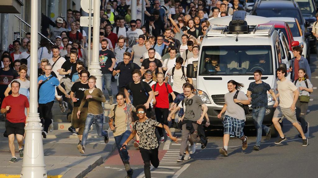 27.07.2019, Russland, Moskau: Demonstranten fliehen vor der Polizei während einer nicht genehmigten Kundgebung im Zentrum   der Stadt. Begleitet von einem massiven Aufgebot der Polizei haben am Samstag in Moskau Hunderte Menschen gegen den Ausschluss