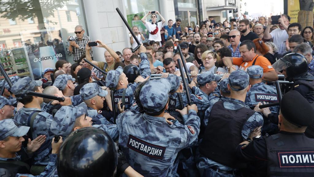27.07.2019, Russland, Moskau: Demonstranten geraten mit der Polizei während einer nicht genehmigten Kundgebung im Zentrum von der Stadt aneinander. Begleitet von einem massiven Aufgebot der Polizei haben am Samstag in Moskau Hunderte Menschen gegen d