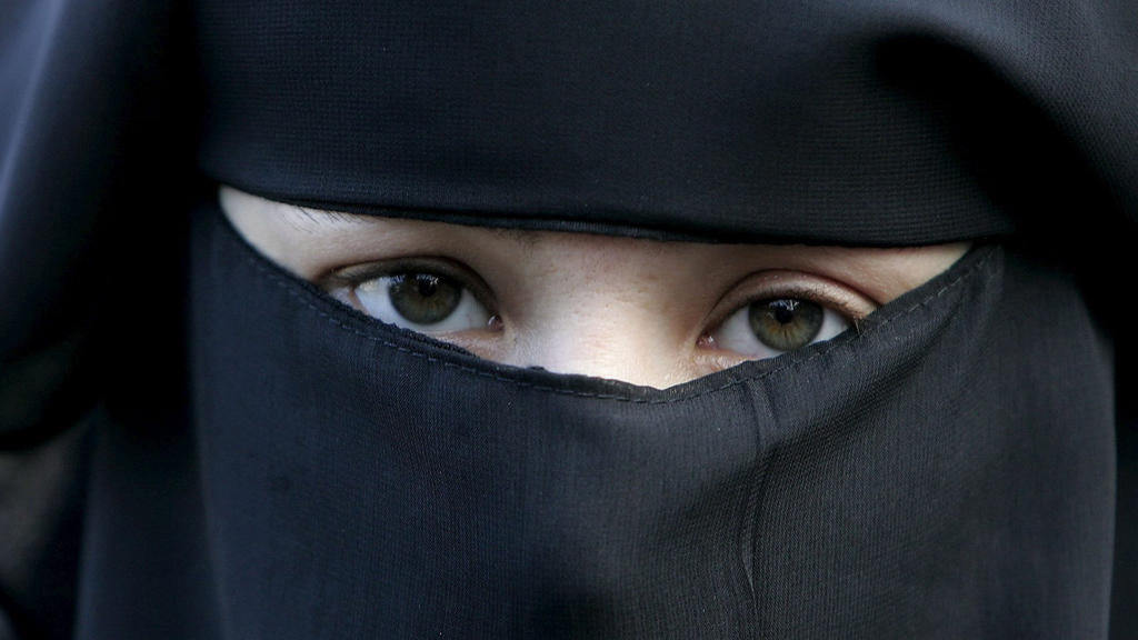 ARCHIV - 30.11.2006, Niederlande, Den Haag: Eine Frau trägt bei einer Demonstration gegen das Verbot einer vollverschleierung einen Nikab. Nach einer heftigen Debatte von mehr als zehn Jahren ist ab Donnerstag 1. August «gesichtsbedeckende» Kleidung