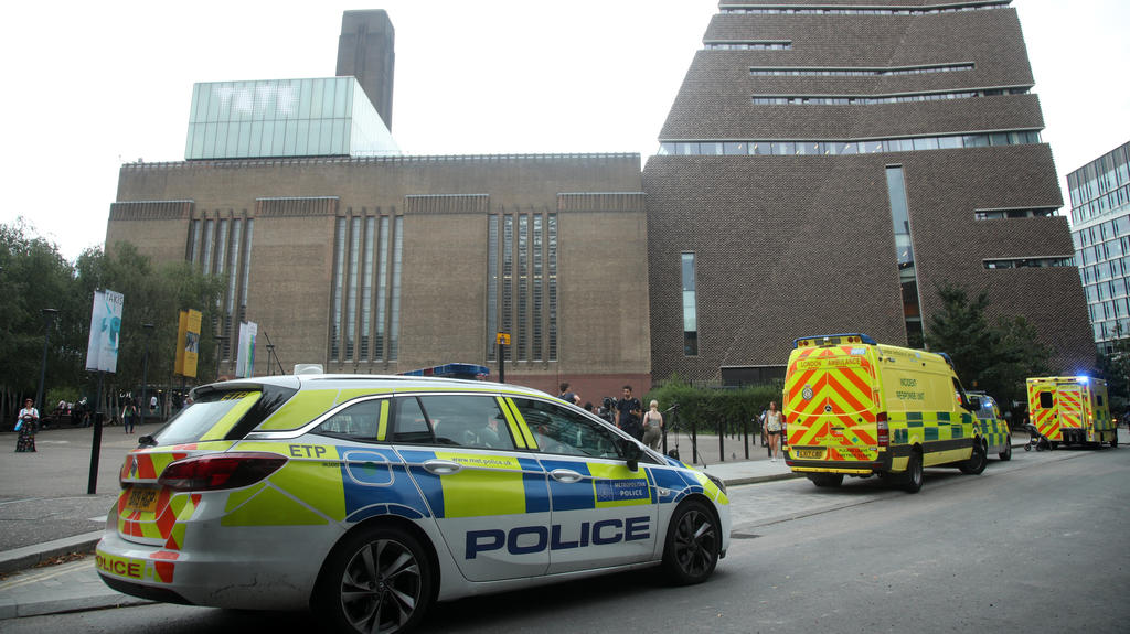 04.08.2019, Großbritannien, London: Einsatzwagen stehen vor dem Tate Modern Museum. Ein 17-Jähriger soll einen sechsjährigen Jungen von einer Aussichtsplattform im zehnten Stock geworfen haben. Der Jugendliche wurde wegen des Verdachts auf versuchten