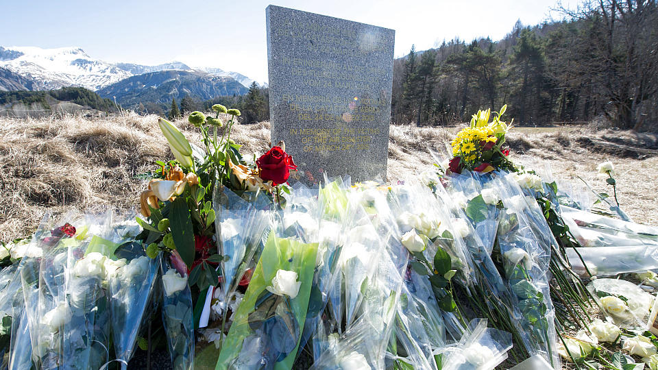 """Inmitten von Blumen steht eine steinerne Gedenkstele mit der Aufschrift """"In Erinnerung an die Opfer des Flugzeugunglücks vom 24. März 2015""""."""