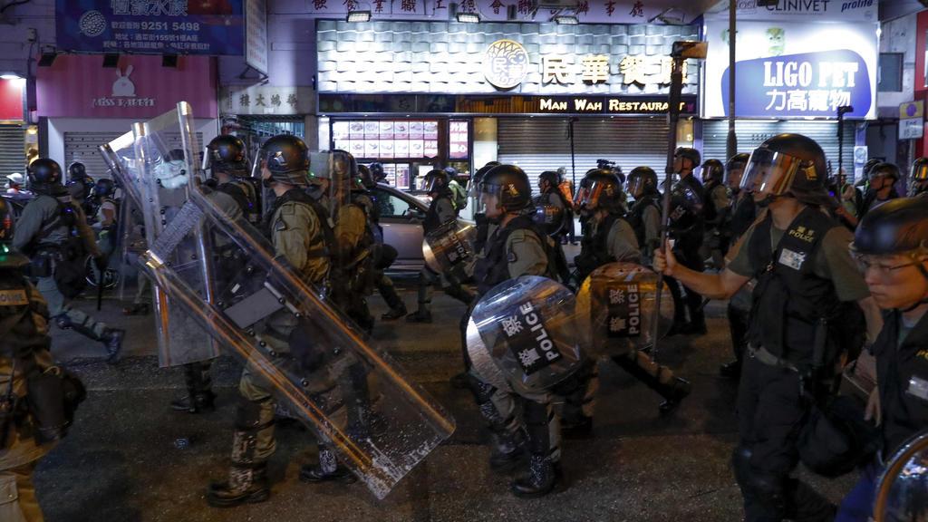 17.08.2019, China, Hongkong: Polizisten in Schutzausrüstung gehen an Läden vorbei während eines Protests prodemokratischer Demonstranten. Mit einer Kundgebung für Freiheit und Demokratie hat am Samstag in Hongkong ein neues Protest-Wochenende begonne