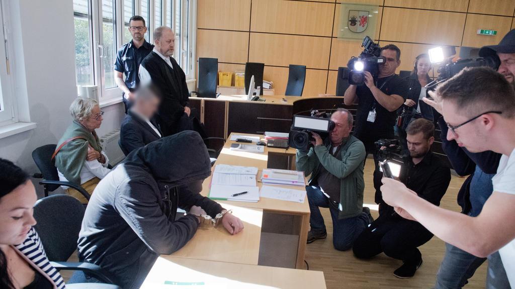 20.08.2019, Mecklenburg-Vorpommern, Stralsund: Der 19-jähriger Angeklagte (2.v.l.) verbirgt im Gerichtssaal im Landgericht sein Gesicht. Für den Mord an der 18-jährigen Maria aus Zinnowitz auf Usedom müssen sich am selben Tag der 19- und ein 21-Jähri