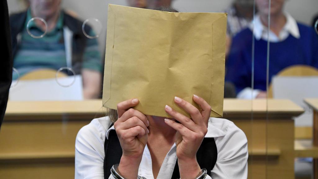 22.08.2019, Schleswig-Holstein, Itzehoe: Mit verdecktem Gesicht sitzt die Angeklagte zum Auftakt eines Mordprozesses im Gerichtssaal. Die 37-Jährige Angeklagte und der 47-Jährige Angeklagte sollen im April 2017 den damaligen Partner der Frau umgebrac