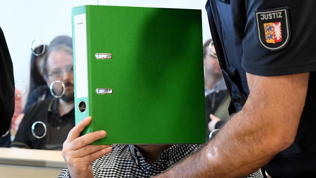 22.08.2019, Schleswig-Holstein, Itzehoe: Mit verdecktem Gesicht sitzt der Angeklagte zum Auftakt eines Mordprozesses im Gerichtssaal. Die 37-Jährige Angeklagte und der 47-Jährige Angeklagte sollen im April 2017 den damaligen Partner der Frau umgebrac