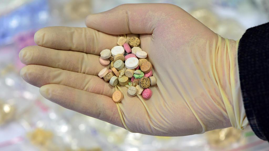 ARCHIV - Ein Ermittler präsentiert am 26.08.2014 im Landeskriminalamt in Erfurt (Thüringen) sichergestellte Ecstasy-Tabletten. In Irland ist der Konsum von Drogen wie Ecstasy, sogenannten Zauberpilzen, Ketamin und anderen Drogen wegen einer Lücke in