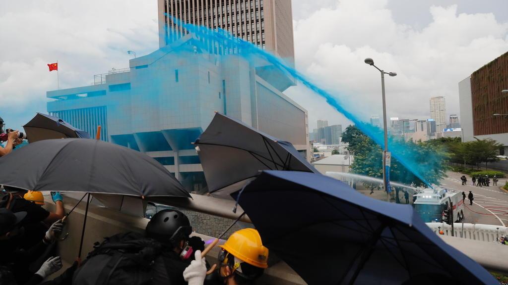 31.08.2019, China, Hongkong: Demonstranten schützen sich mit Regenschirmen vor der Polizei, die mit Wasserwerfern gegen sie vorgeht und die Demonstranten mit blauer Farbe besprüht. Trotz des Verbots einer Großdemonstration kommt es in Hongkong erneut