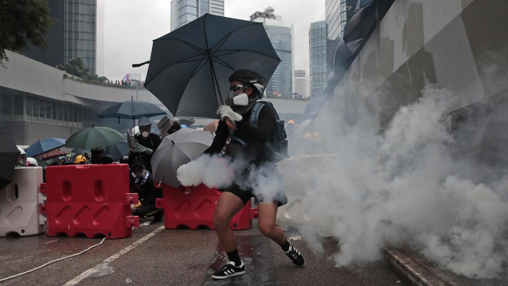 31.08.2019, China, Hongkong: Ein Demonstrant hält eine Tränengasgranate in der Hand. Trotz des Verbots einer Großdemonstration kommt es in Hongkong erneut zu Protesten gegen die Regierung. Foto: Jae C. Hong/AP/dpa +++ dpa-Bildfunk +++