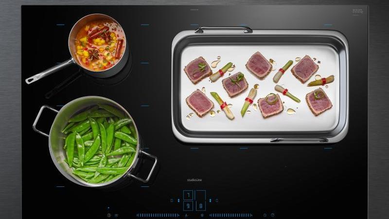 Das neue activeLight-Kochfeld der Serie iQ700 von Siemens und eine smarte Dunstabzugshaube arbeiten im Einklang. Ein integrierter Luftgütesensor registriert die aufsteigende Dunstmenge. Foto: Siemens