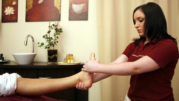 Eine junge Frau bei einer Fußreflexzonenmassage.