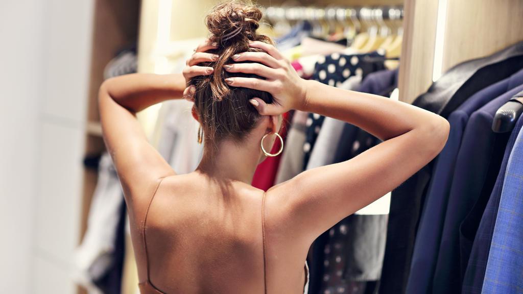 Frau steht verzweifelt vor ihrem Kleiderschrank
