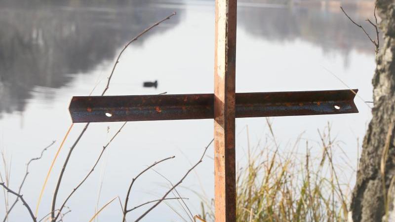 Ein zusammengeschweißtes Metallkreuz steht an einem Gewässer. Foto: Stephanie Pilick