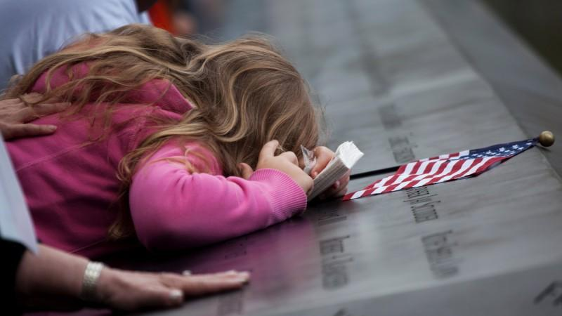 A girl leans over the panels with the victims' names inscribed at the south pool of the 9/11 Memorial during the tenth anniversary ceremonies at the site of the World Trade Center September 11, 2011, in New York, USA. EPA/TODD HEISLER / P