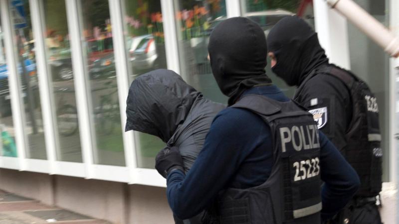Polizeibeamte führen einen Mann ab. Foto: Paul Zinken/Archivbild