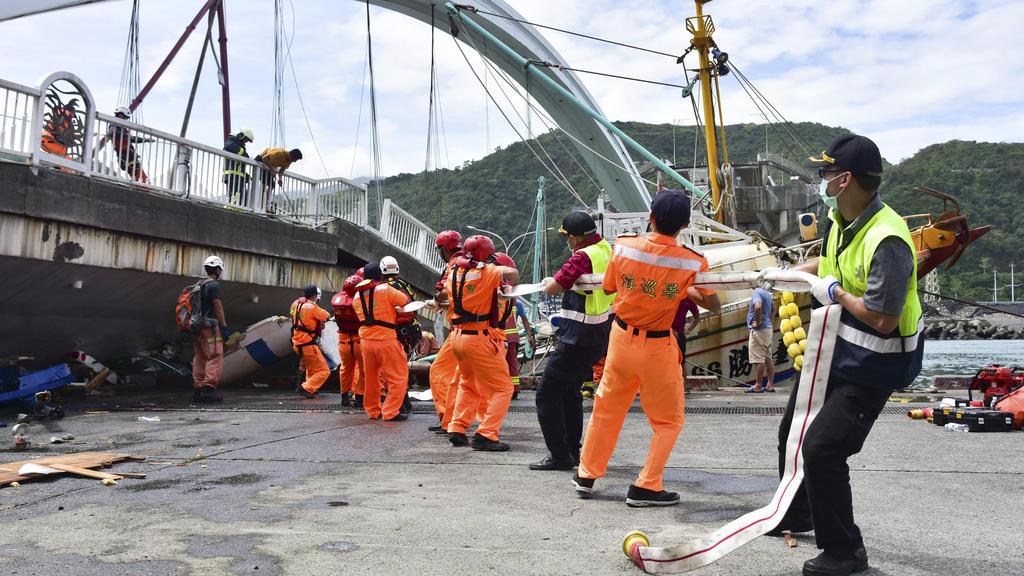 01.10.2019, Taiwan, Nanfangao: Feuerwehrleute und Rettungskräfte arbeiten am Unfallort nach dem Einsturz einer Brücke. Taifun «Mitag» hat in Taiwan eine Brücke einstürzen lassen und auch weitere schwere Schäden hervorgerufen. Nach Angaben der Nationa