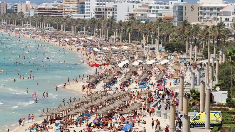 Touristen sonnen sich am Strand von El Arenal auf der Balearen-Insel Mallorca.