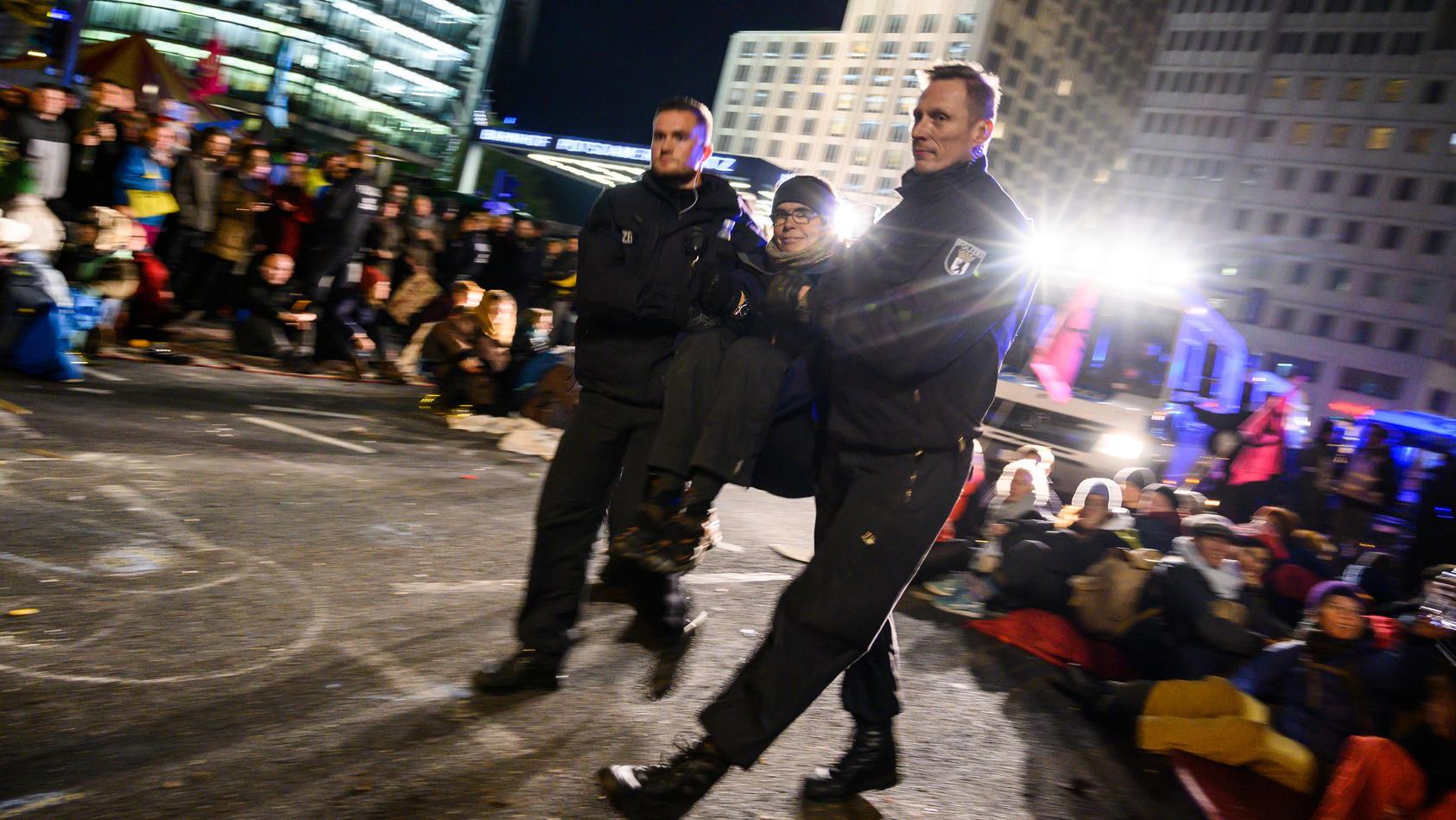 """Polizisten tragen eine Aktivistin der Klimabewegung """"Extinction Rebellion"""" beim Auftakt ihrer Aktionswoche """"Berlin blockieren"""""""
