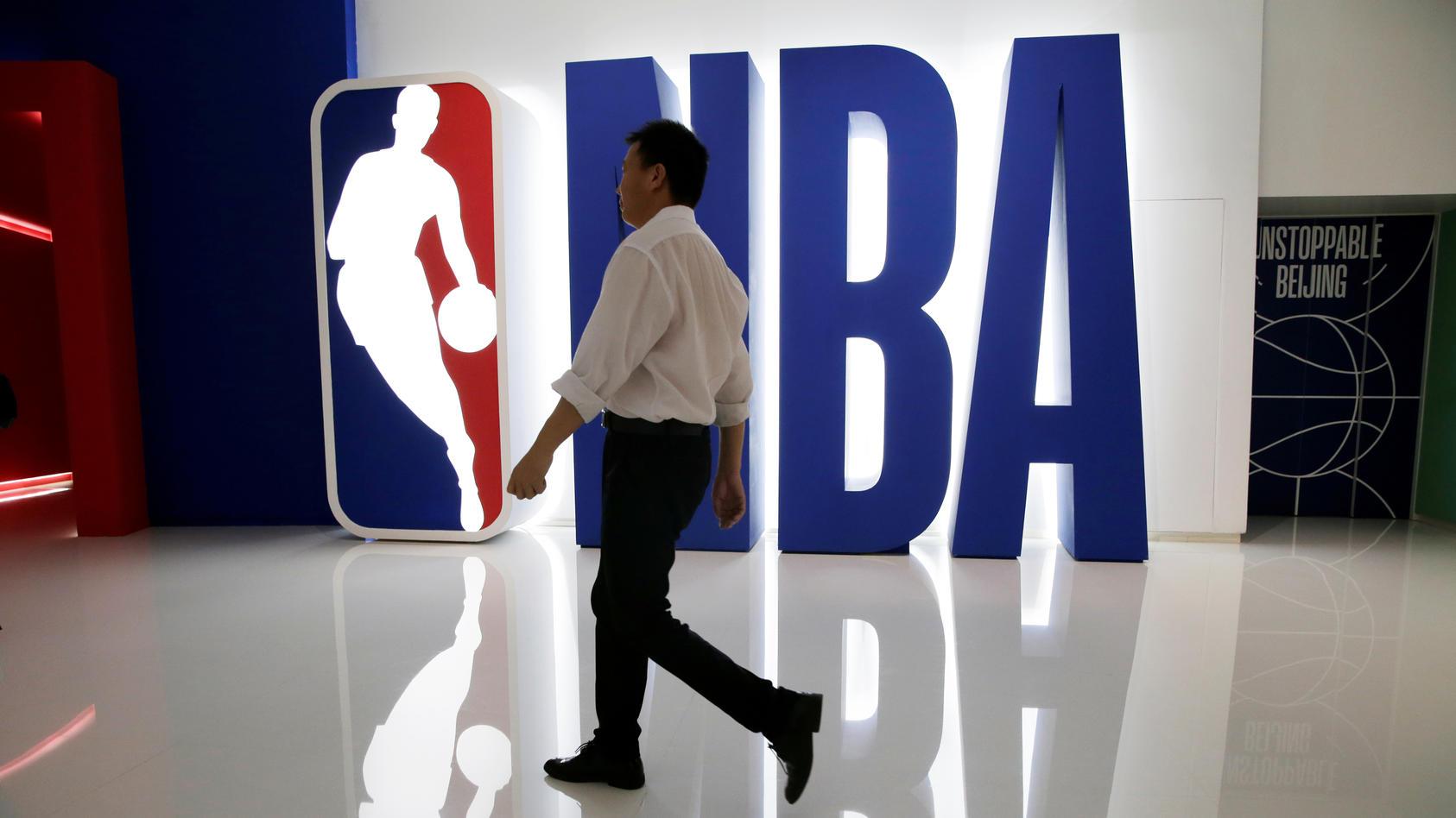 A man walks past an NBA logo at an NBA exhibition in Beijing