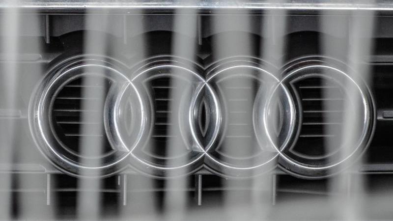 Hinter einem Metallzaun steht ein Audi mit dem Logo des Autoherstellers auf der Motorhaube in einem Parkhaus.