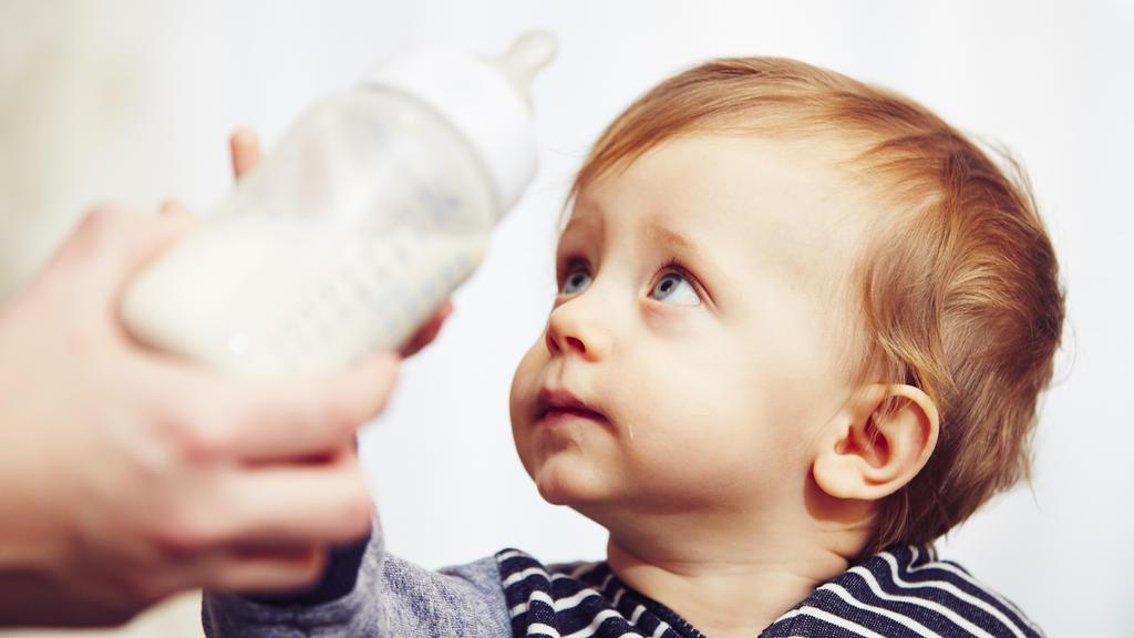 Kleinkind bekommt Flasche mit Milch
