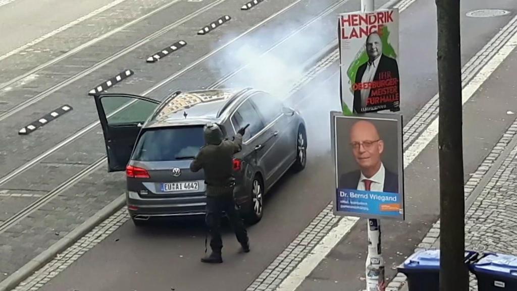 09.10.2019, Sachsen-Anhalt, Halle: In dem Videostandbild steht ein Mann hinter einem Auto und schießt mit einer Waffe auf der Straße. Ein schwerbewaffneter mutmaßlicher Rechtsextremist hatte am Mittwoch versucht, in die Synagoge einzudringen und dort