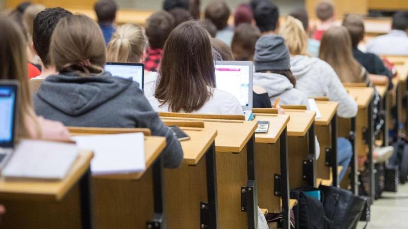 Studierende sitzen mit Laptops an der Universität in einer Vorlesung. Foto: Sebastian Gollnow/dpa