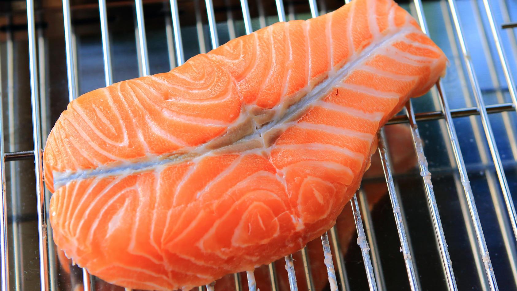 Ein Stück roher Lachs liegt auf einem Elektro-Grill. Lachs gehört heute zu den am meisten geschätzten Speisefischen. Sein orangerosa bis dunkelrotes Fleisch ist reich an Omega-3-Fettsäuren.