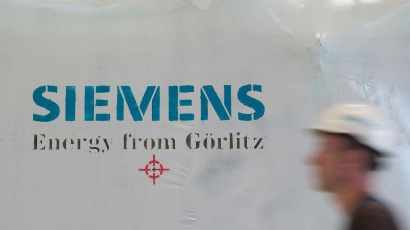 """Ein Siemens-Mitarbeiter mit Schutzhelm geht an einer Folie mit dem Aufdruck """"Siemens Energy from Görlitz"""" vorbei. Foto: Sebastian Kahnert/zb/dpa/Archivbild"""