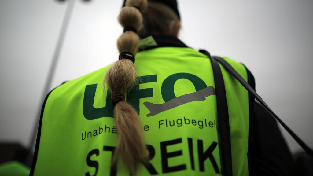 ARCHIV - 27.10.2016, Nordrhein-Westfalen, Köln: Eine Flugbegleiterin steht vor dem Unternehmenssitz von Eurowings bei einer Kundgebung. Erstmals seit vier Jahren wollen Flugbegleiter der Lufthansa an diesem Sonntag streiken. (zu dpa «Gewerkschaft Ufo