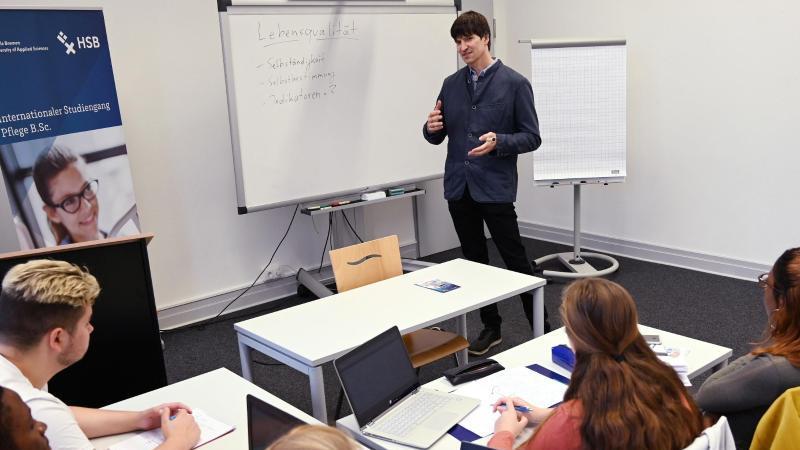 Eckart Seilacher, Dozent im Internationalen Studiengang Pflege, steht an der Tafel. Foto: Carmen Jaspersen/dpa