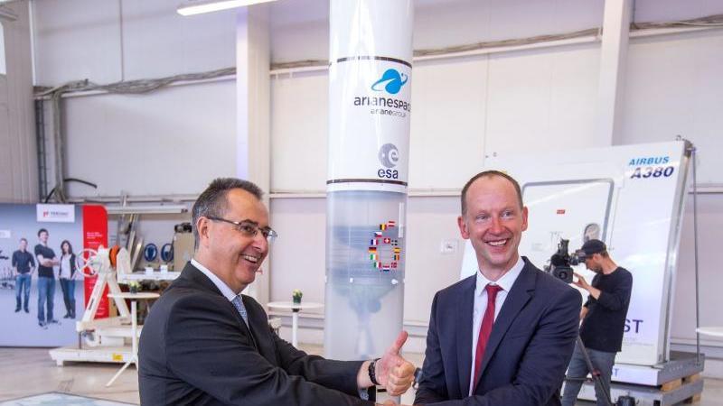 Pierre Godart (l.) mit Martin Sauerschnig, Geschäftsführer der RST, neben dem Modell einer Ariane 6. Foto: Jens Büttner/zb/dpa/Archivbild