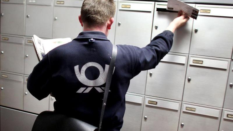 Ein Briefträger der Deutschen Post trägt Briefe aus. Foto: Oliver Berg/Archiv