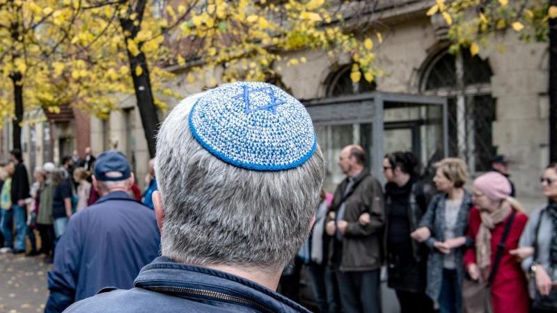 Ein Mann mit Kippa vor der Menschenkette an der Neuen Synagoge. Foto: Paul Zinken/dpa
