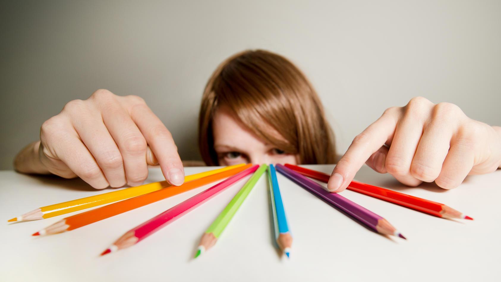 Zwangsstörung: Eine junge Frau zählt die Buntstifte auf ihrem Schreibtisch nach.