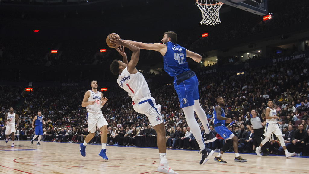 18.10.2019, Kanada, Vancouver: Basketball: NBA, Los Angeles Clippers - Dallas Mavericks, Testspiel: Dallas Mavericks Maxi Kleber (oben) aus Deutschland in Aktio mit Los Angeles Clippers Jerome Robinson (2.v.l). Foto: Darryl Dyck/The Canadian Press/AP