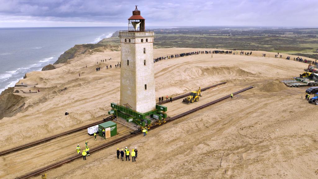 """14.09.2017, Dänemark, Loenstrup: Schaulustige wohnen dem """"Umzug"""" eines rund 120 Jahre alten Leuchtturms bei. Der Leuchtturm Rubjerg Knude Fyr war 1899 auf einer Wanderdüne errichtet worden. Aufgrund der Erosion der Küste drohte er ins Meer zu stürzen"""