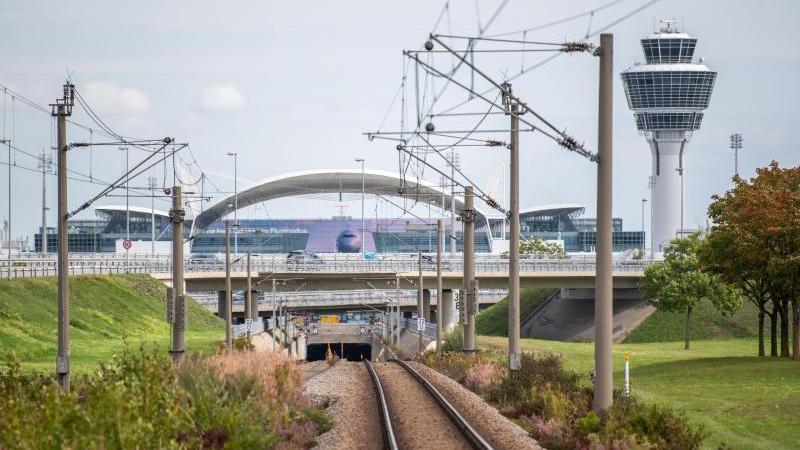 Leere Gleise der S-Bahn führen zum Flughafen München mit dem Tower im Hintergrund. Foto: Lino Mirgeler/dpa