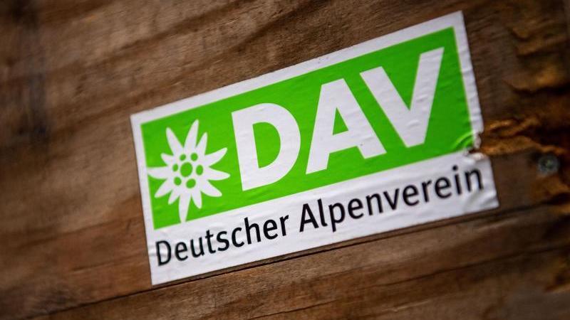 Das Logo des Deutschen Alpenverein (DAV) klebt auf einer Holzbox. Foto: Lino Mirgeler/dpa