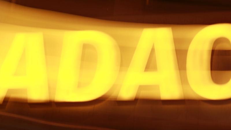 Eine Leuchtreklame von ADAC. Foto: Rene Ruprecht/dpa/Archivbild