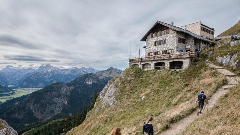 Wanderer gehen zur Bad Kissinger Hütte des Deutschen Alpenvereins (DAV). Foto: Nicolas Armer/dpa/Archivbild