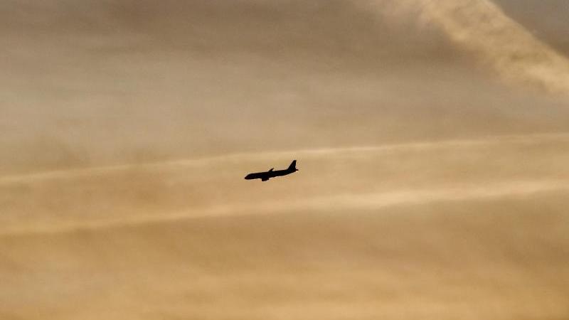 Ein Flugzeug setzt beim Sonnenaufgang zum Landeanflug an. Foto: Julian Stratenschulte/dpa/Archivbild