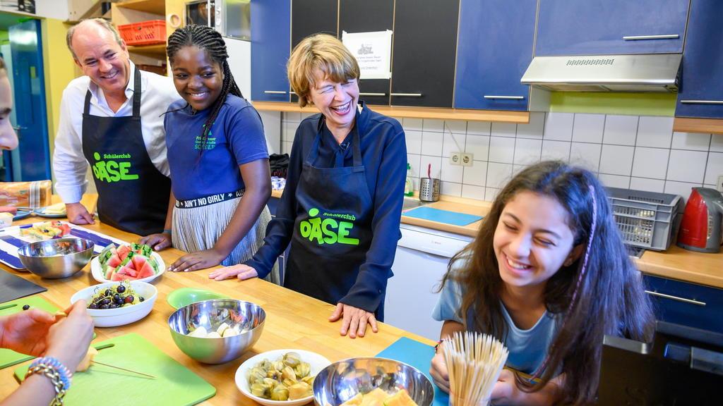 V.l.: Wolfram Kons, Celia und Elke Büdenbender bereiten gemeinsam mit Schülerinnen Pausensnacks für die Schülerfirma 'Pausenkiosk' vor.